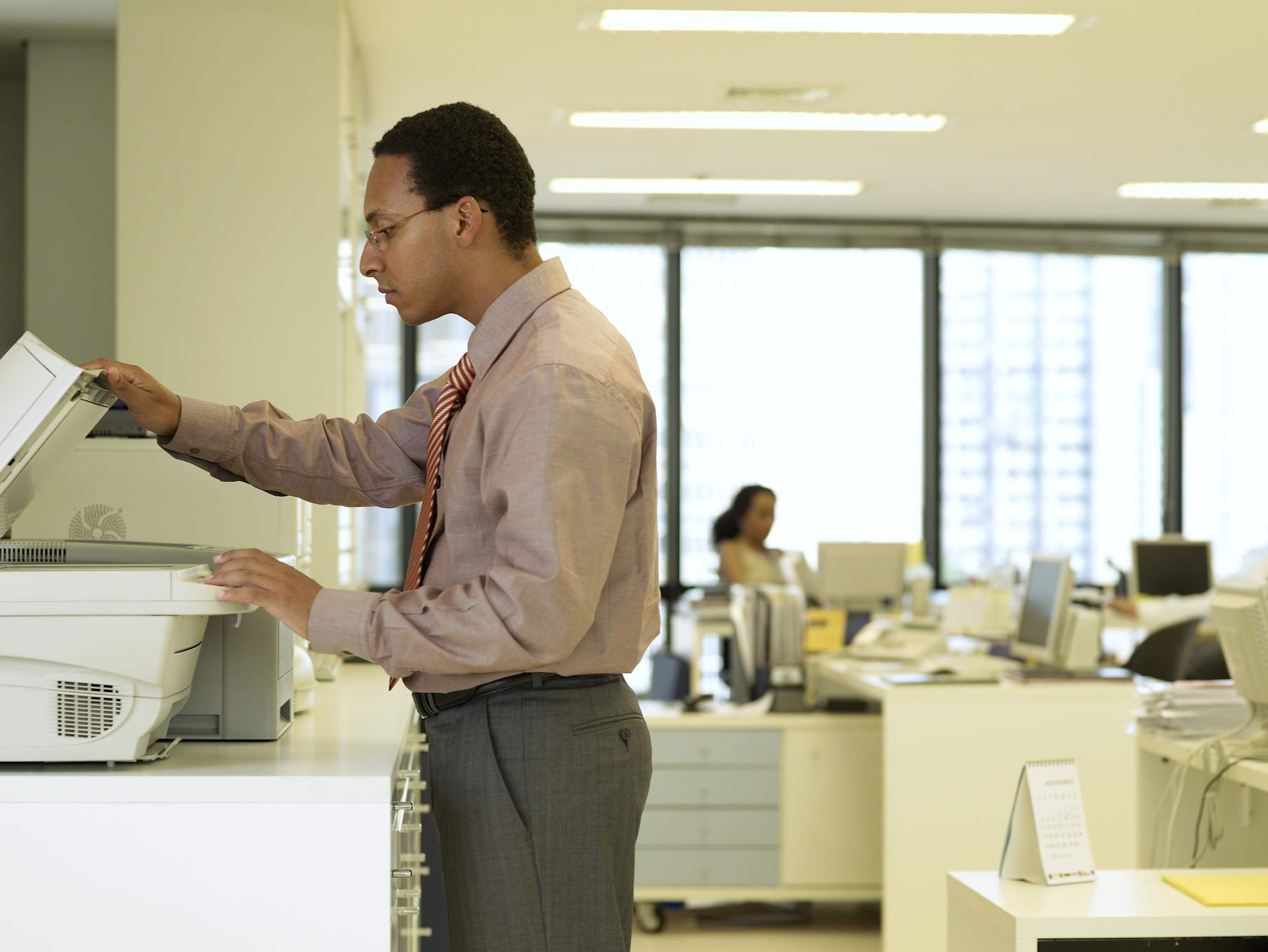 A businessman uses a photocopier in an office.