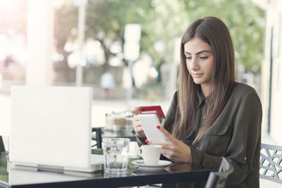 A woman at a cafe table considers how she should pay for her latte: credit account or credit card?