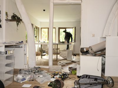 a ransacked house with a robber climbing out a window