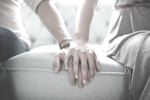 Male and Female Bodies with Hands Over Each Other's Hands on Couch