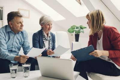 Mature Couple Discussing Documents With Professional