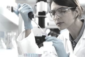 Scientist pipetting sample into a tube for analytical testing in the laboratory