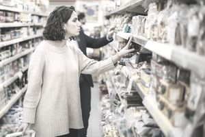 Serious woman looking at cookies in grocery store.