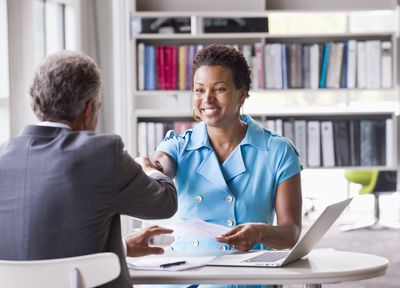 A business woman shakes hands with a banker across a desk after receiving a prime interest rate loan.