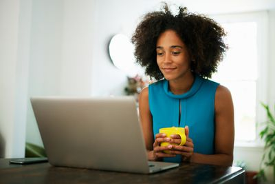 Woman reading on laptop at home holding coffee mug