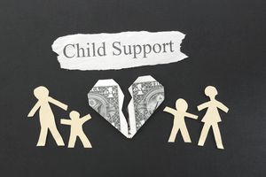 paper cut outs and dollar bill represent child support