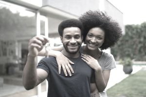 Twenty-something couple proudly displaying the house keys in front their new home