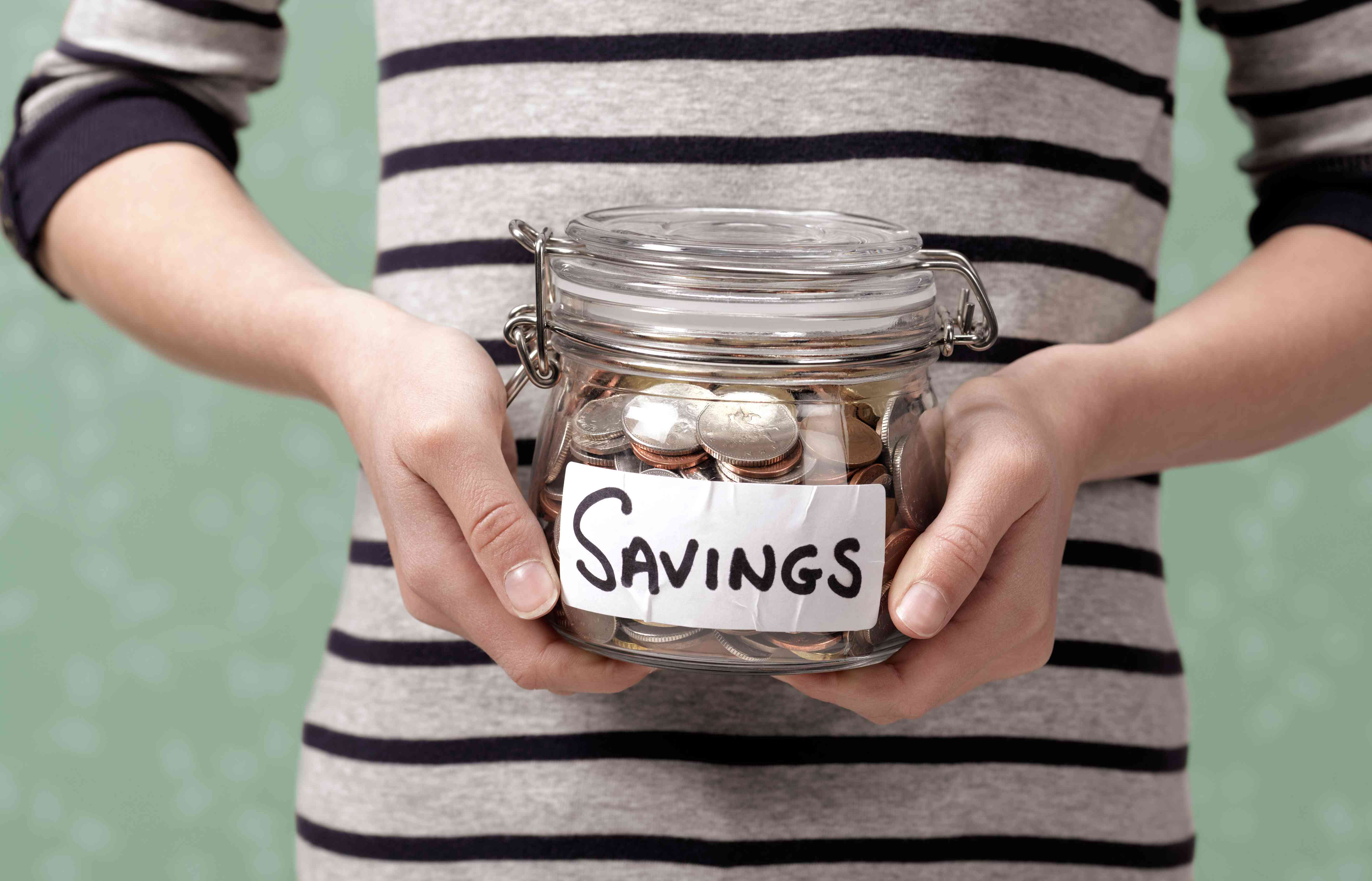 Young person holding savings in jar