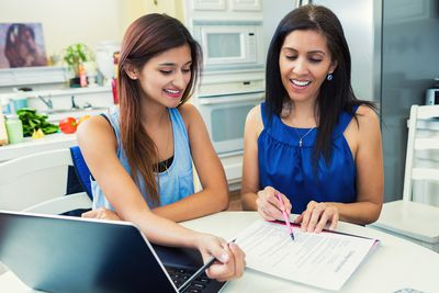 Mom with daughter sitting at a desk reviewing what their 529 plan will cover of the costs