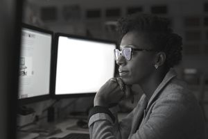 Focused, dedicated businesswoman working late at computers in dark office