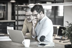 Two confused businessmen look at laptop in office