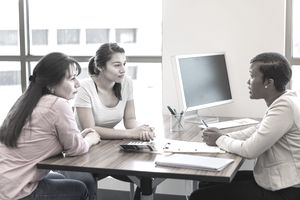 Loan officer talks with Hispanic mother and daughter