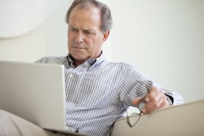 Man with serious expression looks at laptop
