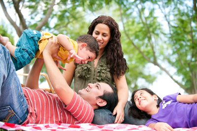 Parents with two young children relaxing in a park