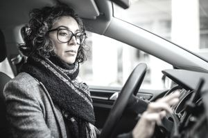A woman sits in the driver's seat of her car, checking her phone for directions