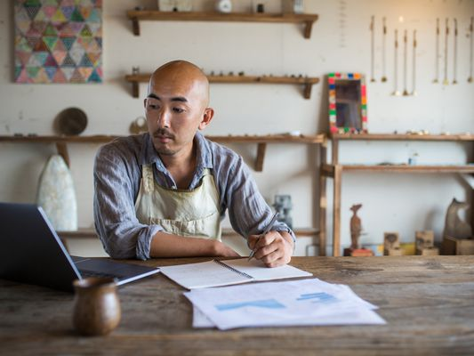 A business owner sits in his shop reviewing his tax forms on paper and on his laptop