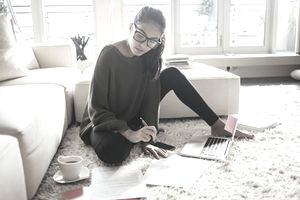 Young woman with laptop and papers on the floor of her living room.