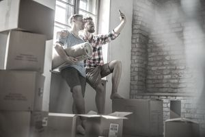 A couple takes a selfie in their new home, surrounded by moving boxes