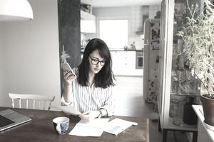 A woman takes stock of her assets with phone, coffee, paperwork at home table