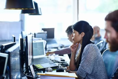 Woman sits at laptop in office with other employees