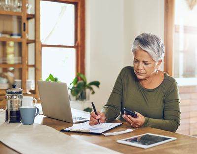 Woman sits at a dining table using a calculator to determine her traditional IRA contribution percentage