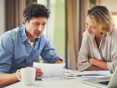 A man and a woman sitting at a dining room table reviewing financial documents