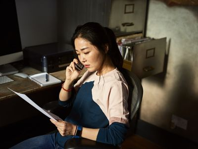 Serious-looking woman speaks on the phone while holding tax documents