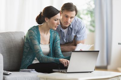 A couple makes a mortgage payment online.