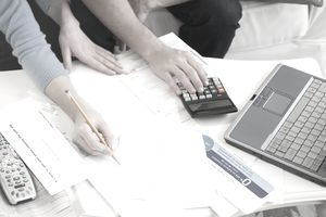 Hands of couple going over financial paperwork and working on a calculator and laptop