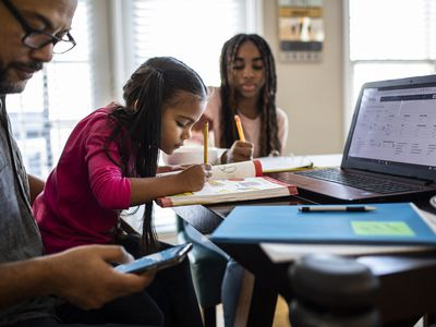 A parent and two children work at the same table.