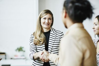 Two women shaking hands in an office setting.