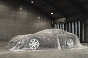 Car in storage sitting in a warehouse, covered in bubble wrap
