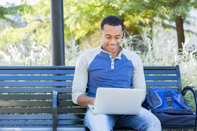A smiling investor working on a laptop on a bench in a park