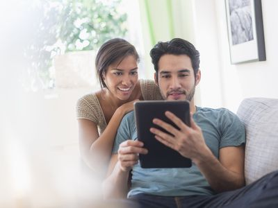 A couple looks at a laptop