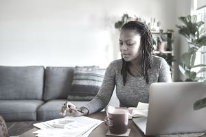 Young woman using a laptop and going through documents while working from home