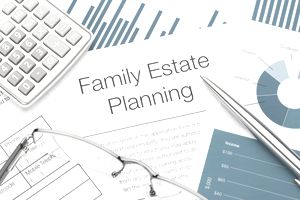 Closeup of a family estate planning document, pen, glasses, and calculator
