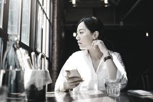 A woman stares out the dusty window of an afternoon cafe, taking a break from staring at the smartphone she clutches in her right hand.