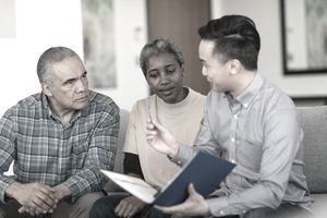Seated older black couple listens to Asian life insurance agent explaining a policy in their living room.
