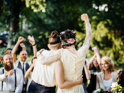 A same sex couple celebrates their marriage in front of their gather family and friends