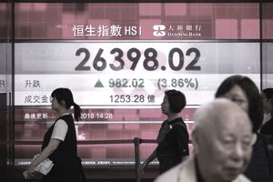 Pedestrians walk past a stocks display board that shows an increase in the Hang Seng Index in Hong Kong on November 2, 2018. - Asian markets enjoyed another rally on November 2 after Donald Trump hailed positive talks with Chinese President Xi Jinping and a report said he had asked officials to draw up a draft bill as he eyes a potential trade deal between the two.