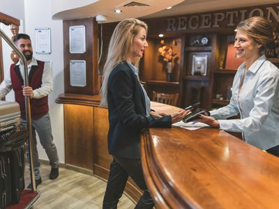 Woman paying with her credit card in a hotel; front desk receptionist is smiling, and bellhop is waiting with her luggage