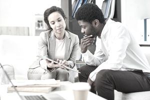 A man and a woman review the prequalification terms of a loan in a modern office