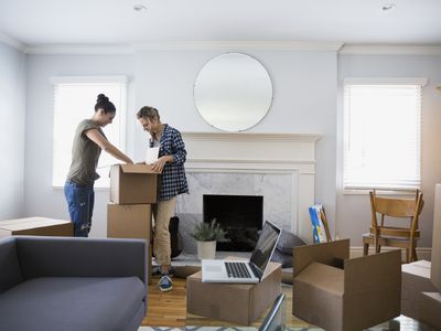Couple in new home unpacking boxes