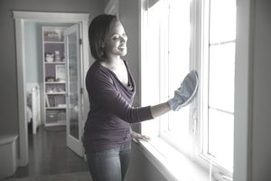 woman cleaning windows with mitt