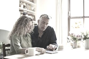Mature couple at dining room table looks at digital tablet
