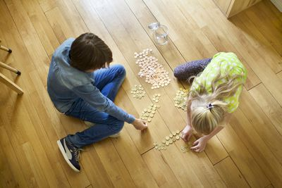 Children counting coins on floor - do kids need life insurance