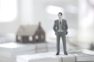 Businessman figurine standing on a stack of money with a house behind him