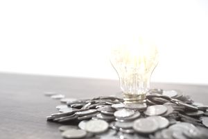Light bulb and pile of coins with copy space