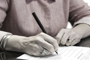 Close-up of a woman's hands signing a will