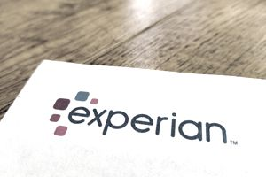 Close-up of Experian credit bureau logo on a credit report, on a wooden table